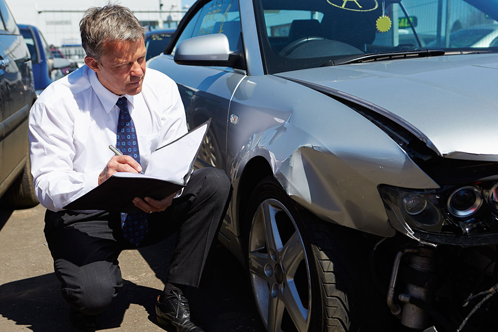 Loss Adjuster Inspecting A Car