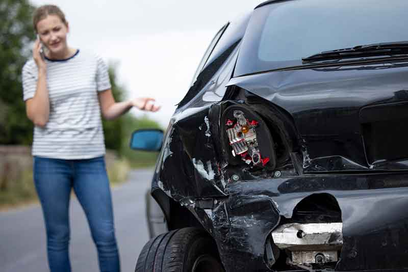 Woman Standing By Crashed Car